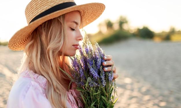 Retrato romántico de cerca o encantadora chica rubia con sombrero de paja huele flores en la playa por la noche, cálidos colores del atardecer. ramo de lavanda. detalles.