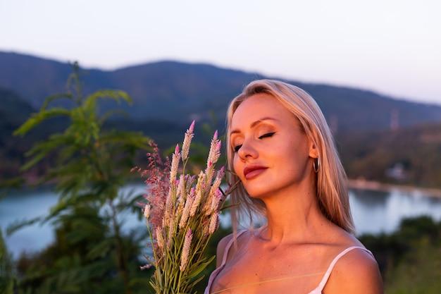 Retrato romántico de joven mujer caucásica en vestido de verano disfrutando de relajarse en el parque en la montaña con increíbles vistas al mar tropical