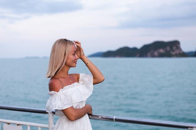 Retrato romántico de mujer en vestido blanco navegando en ferry grande