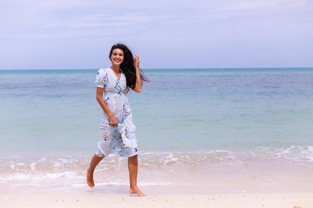 Retrato romántico de mujer con vestido largo azul en la playa por el mar en día ventoso