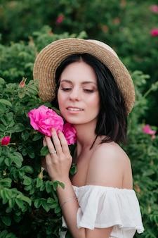 Retrato romántico de primer plano o encantadora mujer morena con sombrero de paja huele a flores en rosales