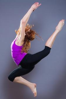 Retrato de ropa deportiva hermosa joven trabajando en fondo gris. colocar chica deportiva haciendo yoga avanzado, pilates, fitness.