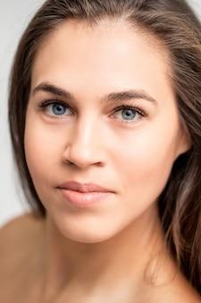 Retrato de rostro de joven mujer caucásica con maquillaje natural y extensiones de pestañas mirando a cámara sobre fondo blanco.
