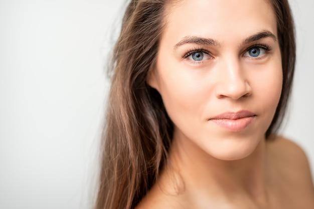 Retrato de rostro de mujer caucásica joven con maquillaje natural y extensiones de pestañas en la pared blanca