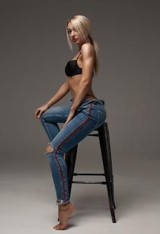 Retrato de una rubia hermosa y sexy con una gran figura que usa jeans de marca azul que nos muestra su tentador vientre. aislado sobre fondo gris