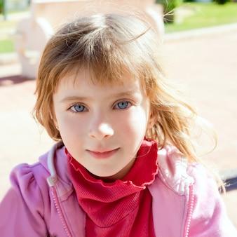 Retrato rubio de los ojos azules de la niña en rosa