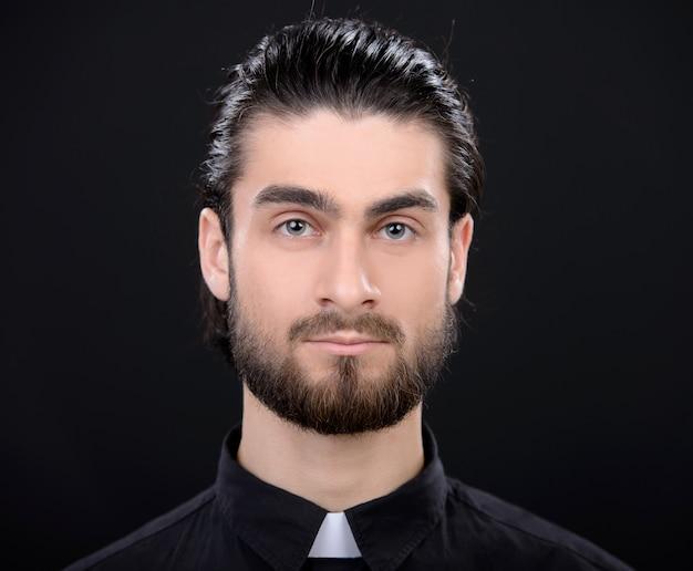 Retrato del sacerdote que se coloca aislado en negro.