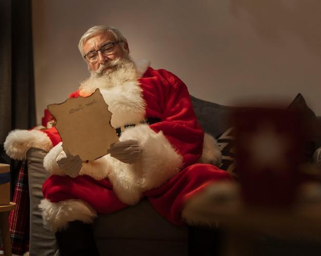 Retrato de santa claus leyendo carta de navidad