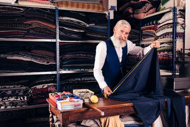 Retrato de un sastre de sexo masculino mayor que toma la medida de la tela azul con la cinta métrica en la tabla en su tienda