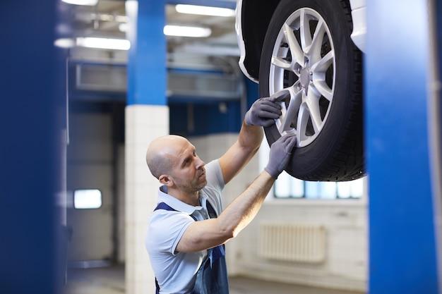 Retrato de sección alta de mecánico de automóviles calvo comprobando las ruedas del vehículo en el elevador de automóviles durante la inspección en la tienda del garaje, espacio de copia