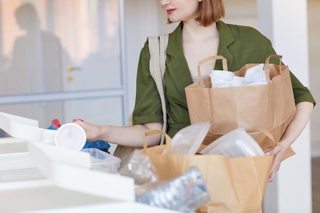 Retrato de la sección intermedia de la mujer joven moderna clasificación de artículos de plástico en casa, listos para su reciclaje
