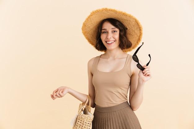 Retrato de seductora mujer morena con sombrero de paja posando con bolsa de verano y gafas de sol en la mano aislado