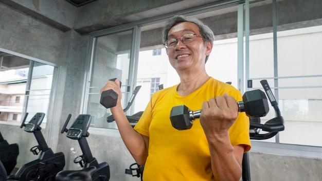 Retrato de senior con anteojos haciendo ejercicio en el gimnasio.