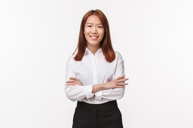Retrato de señora jefa profesional inteligente y creativa, empresaria en camisa blanca elegante, cruza las manos sobre el pecho y sonríe satisfecho, dirige negocios exitosos,