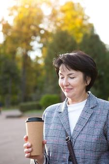 Retrato de la señora en el parque con una taza de café de plástico reutilizable. reciclaje y ecología, residuo cero. un paseo al aire libre, una edad feliz durante 50 años.