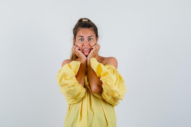 Retrato de señorita almohada cara en sus manos en vestido amarillo y mirando preocupado vista frontal