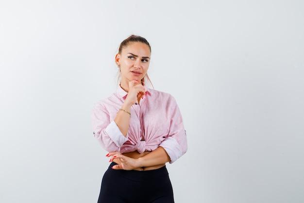 Retrato de señorita apoyando la barbilla en la mano en camisa, pantalones y mirando pensativo vista frontal