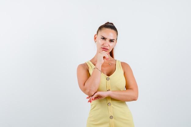 Retrato de señorita apoyando la barbilla en la mano con vestido amarillo y mirando pensativo vista frontal