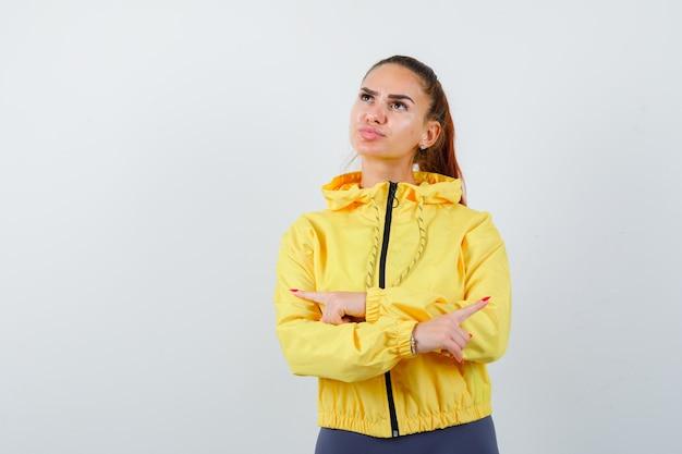 Retrato de señorita apuntando hacia los lados izquierdo y derecho, haciendo pucheros con los labios en una chaqueta amarilla y mirando confiada vista frontal