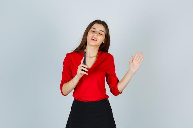 Retrato de señorita disfrutando mientras sostiene el teléfono móvil en blusa roja