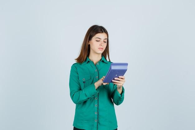 Retrato de señorita haciendo cálculos en la calculadora en camisa verde y mirando ocupado vista frontal