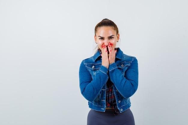 Retrato de señorita con las manos en la boca en camisa, chaqueta y mirando alegre vista frontal