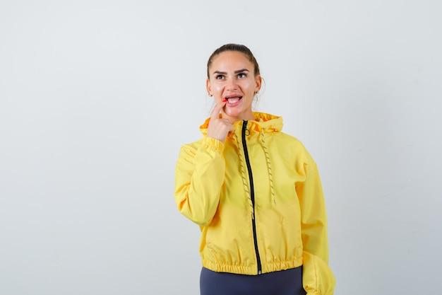 Retrato de señorita manteniendo el dedo en el labio mientras mira hacia arriba con chaqueta amarilla y mirando pensativo vista frontal