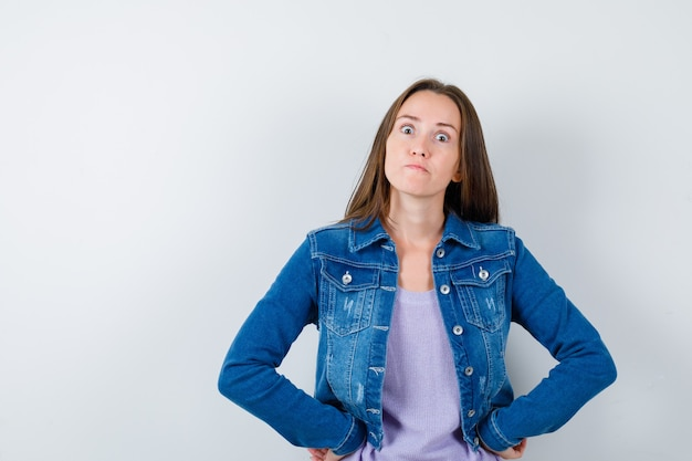 Retrato de señorita manteniendo las manos en la cintura en camiseta, chaqueta y mirando enojado vista frontal