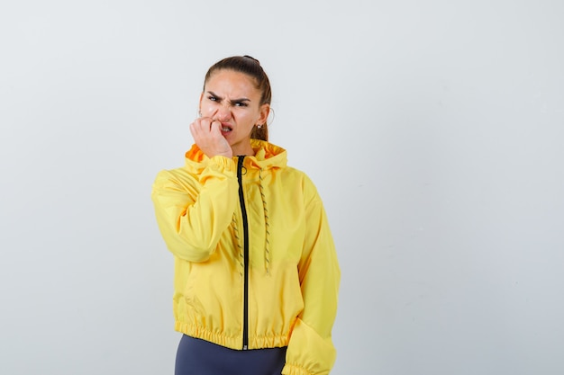 Retrato de señorita mordiéndose las uñas en chaqueta amarilla y mirando nervioso vista frontal