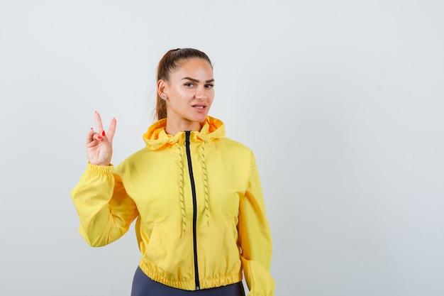 Retrato de señorita mostrando gesto de victoria en chaqueta amarilla y mirando confiada vista frontal