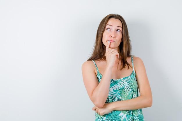 Retrato de señorita de pie en pose de pensamiento en blusa y mirando indeciso vista frontal