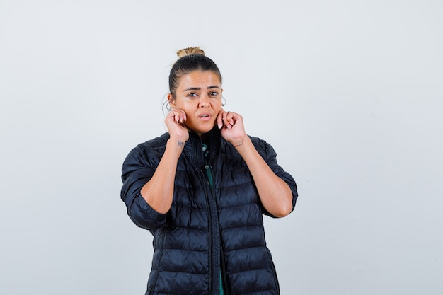 Retrato de señorita tocando las mejillas con las manos en chaqueta acolchada y mirando sensible vista frontal