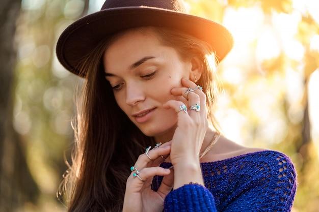 Retrato de sensual y atractiva mujer boho chic con sombrero marrón y suéter de punto con collar y anillos de plata con piedra turquesa. chica elegante joyería de moda con moda boho
