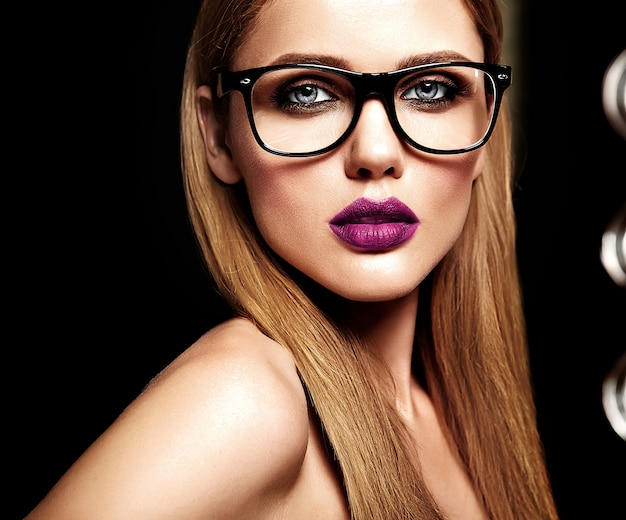 Retrato sensual de glamour de la hermosa modelo de mujer rubia con maquillaje diario fresco con color púrpura de labios y piel limpia y saludable en gafas