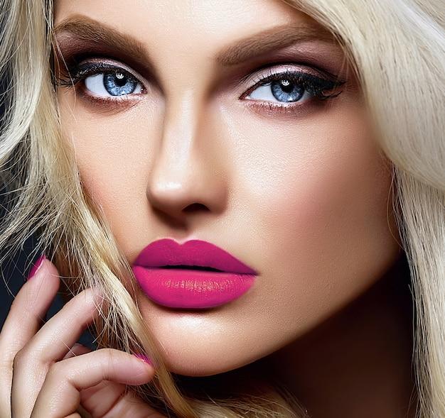 Retrato sensual glamour de hermosa mujer rubia modelo dama con maquillaje brillante y labios rosados, con cabello rizado saludable sobre fondo negro