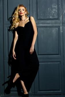 Retrato sensual glamour de hermosa mujer rubia modelo dama con maquillaje fresco en traje negro clásico de pie cerca de la pared