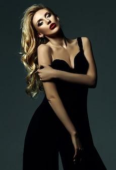 Retrato sensual glamour de hermosa mujer rubia modelo dama con maquillaje fresco en traje negro clásico