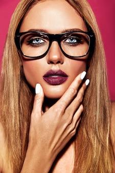Retrato sensual glamour de hermosa mujer rubia modelo con maquillaje diario fresco con color púrpura de labios y piel limpia y sana en vasos sobre fondo rosa