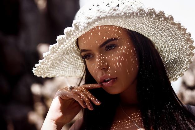 Retrato de sensual morena de ojos marrones en un sombrero de paja con una hermosa sombra en su rostro