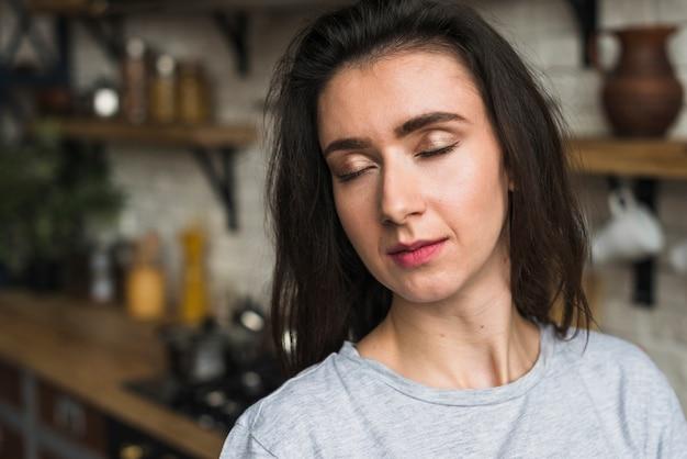 Retrato de una sensual mujer lesbiana de pie en la cocina