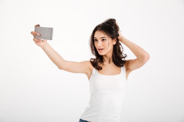 Retrato de una sensual mujer vestida con una camiseta sin mangas tomando una selfie