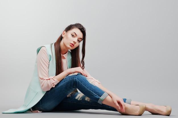 Retrato sentado joven morena con blusa rosa, chaqueta turquesa, jeans rotos y zapatos crema sobre fondo gris