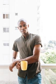 Retrato serio de un hombre africano joven que se coloca en el balcón que sostiene la taza de café amarilla