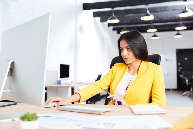 Retrato, de, un, serio, joven, mujer de negocios, utilizar, computador portatil, en, oficina