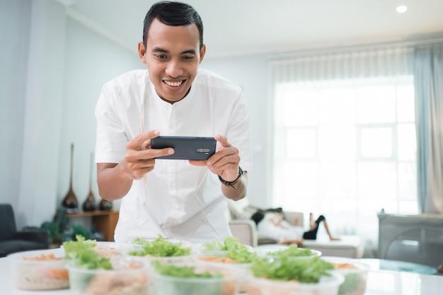 Retrato de servicio de catering a domicilio masculino preparando lonchera para comida para llevar pedido en línea