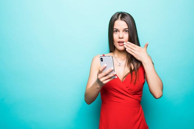 Retrato si una joven conmocionada vestida mirando el teléfono móvil aislado sobre la pared azul