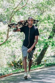 Retrato de un skater masculino joven que sostiene el monopatín en el hombro que camina en el parque
