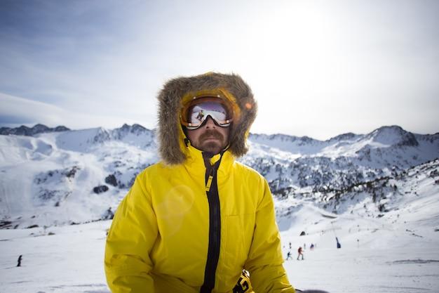 Retrato de snowboarder o esquiador fresco y áspero, o montañero en chaqueta amarilla de invierno cálido