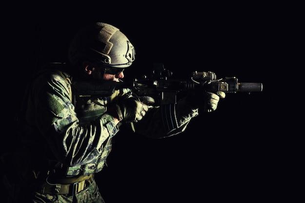 Retrato de soldado de las fuerzas especiales en uniformes de campo con armas, retrato en negro