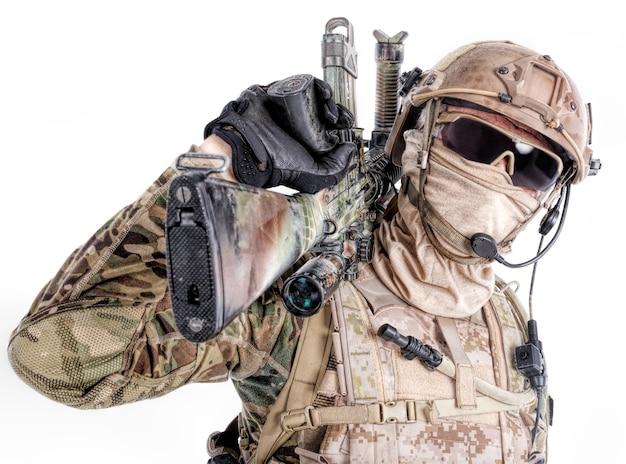 Retrato de soldado de las fuerzas especiales en uniformes de campo y mascarilla con rifle de francotirador en el hombro